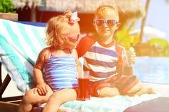 孩子在热带海滩胜地和饮料放松 库存照片