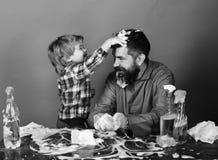 孩子在父亲上把泡沫放朝向并且获得乐趣 家庭时间概念 有儿子和清洁物品的爸爸在绿色背景 免版税图库摄影