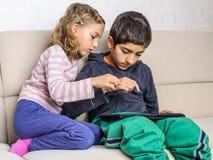 孩子在片剂个人计算机接触 库存图片