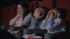 孩子在电影院被吓唬 害怕的儿童盖子面孔用人工 股票录像