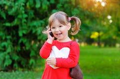 孩子在电话里说在公园 免版税图库摄影