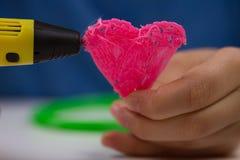 孩子在白色背景递拿着与细丝的黄色3D打印笔并且做心脏 顶视图 复制空间为 免版税库存照片