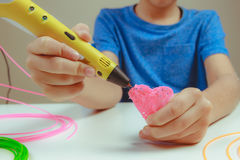 孩子在白色背景递拿着与细丝的黄色3D打印笔并且做心脏 顶视图 复制空间为 免版税图库摄影