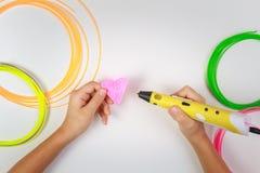 孩子在白色背景递拿着与细丝的黄色3D打印笔并且做心脏 顶视图 复制空间为 库存照片