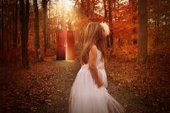 孩子在看发光的红色门的森林 免版税库存照片