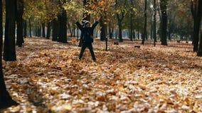 孩子在秋天公园投掷黄色叶子 使用与秋叶,在慢动作的投掷的叶子的愉快的小男孩 影视素材