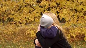 孩子在秋天公园轻轻地拥抱她的母亲 影视素材