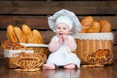 孩子在篮子背景中烹调一个新月形面包与卷和面包的 图库摄影
