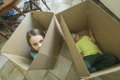 孩子在纸板箱坐 打开箱子和搬入一个新的家 图库摄影