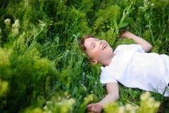 孩子在草说谎 库存图片