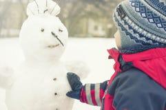 孩子在街道,红色总体的一个男孩上的冬天雕刻一个雪人 库存照片