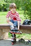 孩子在长凳上把溜冰鞋放 免版税库存照片