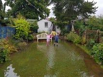 孩子在风暴之后的被充斥的庭院里 免版税库存图片
