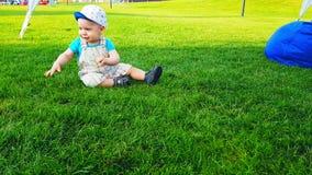 孩子在鲜绿色的草坪和秋天笨拙地走 影视素材