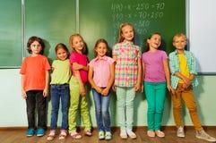 孩子在黑板和微笑附近站在队中 库存照片