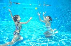 孩子在水池游泳在水面下,女孩获得乐趣在水中, 库存图片