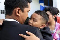 孩子在他的伯父` s膝部哭泣 免版税库存照片