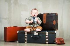 孩子在他的手上坐在手提箱和与一台照相机 免版税库存图片
