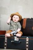 孩子在他的手上坐在手提箱和与一台照相机 库存照片