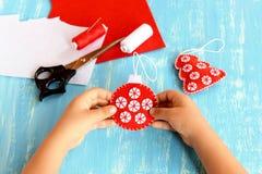孩子在他的手上拿着一个圣诞树球 被绣的红色和白色球装饰品 毛毡板料,螺纹,针,剪刀 免版税库存图片