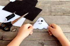 孩子在他的手上拿着一个毛毡鬼魂玩具 毛毡覆盖,剪刀,在一张老木桌上的螺纹 毛毡万圣夜鬼魂装饰品 库存图片