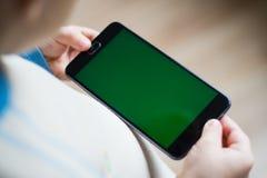 孩子在他的手上拿着一个电话有一个绿色屏幕的为 免版税图库摄影