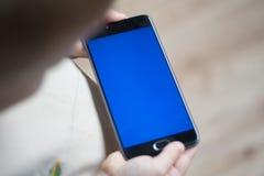 孩子在他的手上拿着一个电话有色度的蓝色的 免版税图库摄影