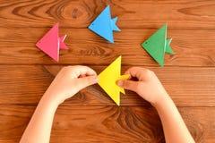 孩子在他的手上拿着一条origami鱼 套在一张木桌上的五颜六色的origami鱼 库存照片