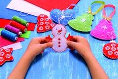 孩子在他的手上拿着一件毛毡雪人装饰品 圣诞节缝合的工艺概念 圣诞树,心脏,星,雪人工艺 免版税库存图片