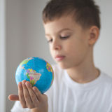 孩子在他的手上的举行玩具globus 免版税库存照片