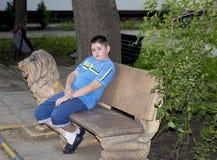孩子坐一条石长凳在公园 免版税库存照片