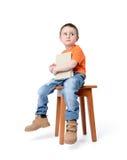 孩子坐与一本书的一把椅子,在白色背景 免版税图库摄影