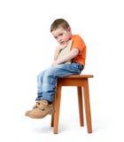 孩子坐与一本书的一把椅子,在白色背景 免版税库存图片