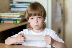 孩子坐与嘴被密封的磁带 库存图片