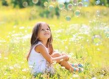 孩子坐作梦在晴朗的夏天的草 库存照片