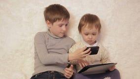 孩子坐使用在您的片剂和电话的长沙发 影视素材