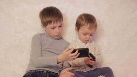 孩子坐使用在您的片剂和电话的长沙发 股票视频