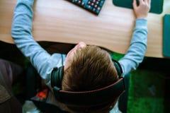 孩子坐在计算机并且打在耳机的电脑游戏 拿着老鼠和键盘的手的顶视图 库存图片