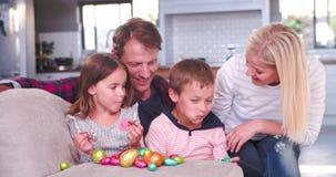 孩子坐有吃复活节彩蛋的父母的沙发 股票视频