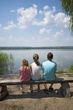 孩子坐湖边 免版税库存图片