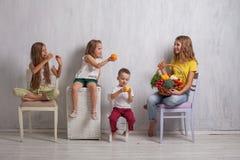 孩子坐用新鲜蔬菜健康吃果子 免版税库存照片