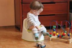 孩子坐罐并且演奏玩具 一个快活的小男孩学会 免版税库存图片