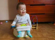 孩子坐罐并且演奏玩具 一个快活的小男孩学会 免版税库存照片