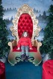 孩子坐金黄和红色王位 库存图片