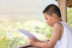 孩子坐阅读书在家发现知识 免版税库存图片