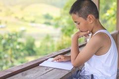 孩子坐阅读书在家发现知识 图库摄影