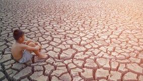 孩子坐破裂的地球 免版税库存图片