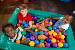 孩子大角度画象坐球水池 免版税库存图片
