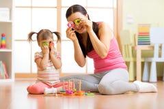 孩子女孩和母亲获得使用与难题玩具一起的一个乐趣 免版税库存照片