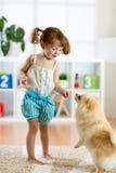 孩子女孩和逗人喜爱的狗在家 免版税图库摄影